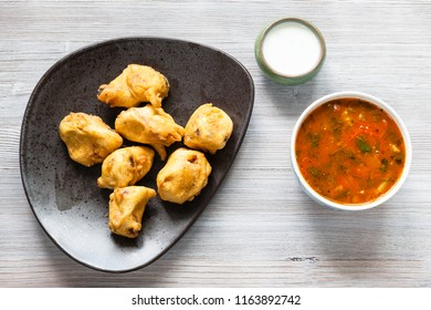 Indian cuisine - Chicken Pakoda pieces dipped in spiced butter on black plate served with sambar and chutney sauces on gray wooden board