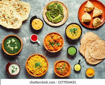 Indian cuisine dishes: tikka masala, dal, paneer, samosa, chapati, chutney, spices. Indian food on gray background. Assortment indian meal top view or flat lay.