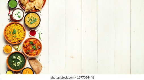 Indian cuisine dishes: tikka masala, dal, paneer, samosa, chapati, chutney, spices. Indian food on white wooden background. Assortment indian meal banner with copy space for text. Top view or flat lay