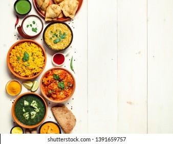 indische Küche: Ttikka masala, dal, paneer, samosa, chapati, chutney, Gewürze. indisches Essen auf weißem Holzhintergrund. Sortiment indianisches Gericht mit Kopienraum für Text. Draufsicht oder flache Lage.