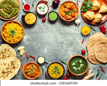 Indian cuisine dishes: tikka masala, dal, paneer, samosa, chapati, chutney, spices. Indian food on gray background. Assortment indian meal with copy space for text in center. Top view or flat lay.