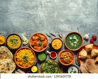 Indian cuisine dishes: tikka masala, dal, paneer, samosa, chapati, chutney, spices. Indian food on gray background. Assortment indian meal with copy space for text. Top view or flat lay.