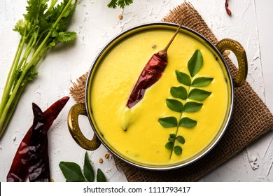Indian Cuisine Kadhi - Vegetarian Curry Made of Buttermilk And Chick Pea Flour. served in a bowl or Karahi over moody background, selective focus