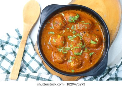 Indian cuisine - Kashmiri Dum Aloo or Potatoes in red gravy over white background. Garnished with coriander. Serve hot with rice or Naan/roti. Copy space. Panjabi Dam alu curry. - Shutterstock ID 1829475293