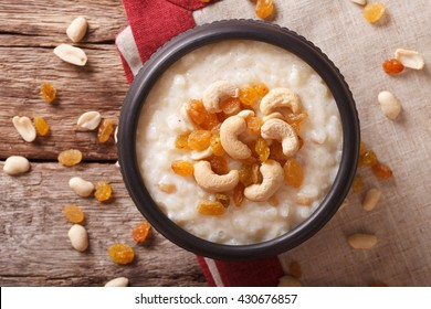 Indian cuisine: kheer rice pudding with nuts and raisins in a bowl close-up on the table. Horizontal view from above