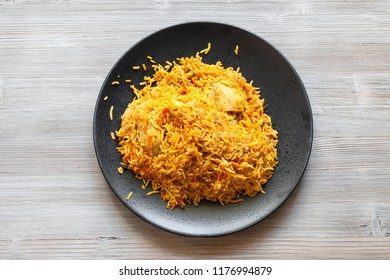 Indian cuisine - Murg Sindh Biriyani spicied chicken pulao cooked with potato in DUM style in tandoor on black plate on wood board