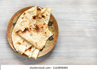 Indian cuisine - Naan flat bread baked in tandoor on brass plate on gray wood board