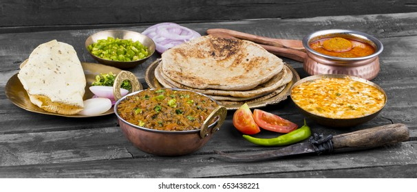 Indian Cuisine Sev Tamatar Also Called Sev Tamaeta or Sev Tameta is Served With Chapati, Papad, Onion or Raita. It is Made With Tomato And Onion Gravy With a Twist of Spicy Sev on Wooden Table