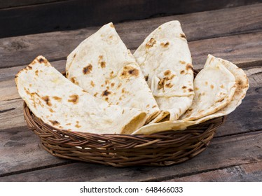 Indian Cuisine Tandoori Roti Served in Basket Also Called Chapati, Flatbread, Naan or Nan Bread on Wooden Background