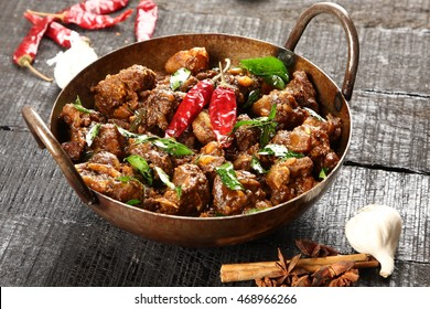 Indian cuisine-Famous Indian mutton or lamb curry dish in a cast iron cookware. Selective focus photograph.