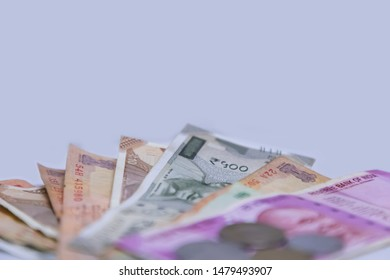 Indian currency bank notes of  500 and 2000 rupees with coins - white background with space for text