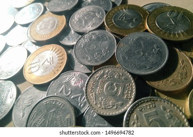Indian currency, stack of Indian coins of one, five and ten rupees, money photography in a white marble background, economy