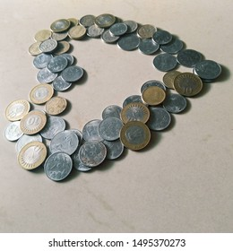 Indian currency, tilted heart shaped stack of Indian coins of one, five and ten rupees, money photography in a white marble background, economy