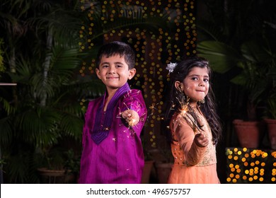 indian cute Boy and girl in traditional wear playing with sparklers or fulzadion diwali night