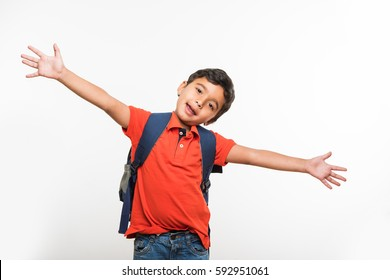 indian cute kid or boy leaving or going to school with small school bag, isolated over white background