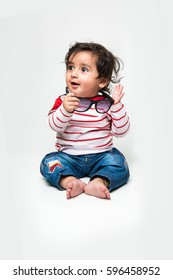 Indian cute little baby /infant or toddler playing with toys or blocks over white background,