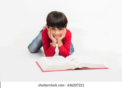 indian cute little boy or kid reading book while sitting or lying over white background
