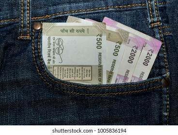 Indian cuurency notes INR peeping out of the front pocket ofblue jeans.