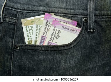 Indian cuurency notes INR peeping out of the front pocket of black jeans.
