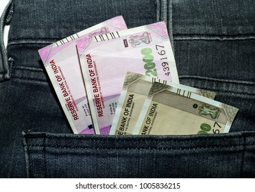 Indian cuurency notes INR peeping out of the back pocket of black jeans.