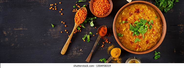 Indian dal. Food. Traditional Indian soup lentils.  Indian Dhal spicy curry in bowl, spices, herbs, rustic black wooden background. Top view. Authentic Indian dish. Overhead. Banner
