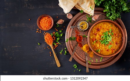 Indian dal. Food. Traditional Indian soup lentils.  Indian Dhal spicy curry in bowl, spices, herbs, rustic black wooden background. Top view. Authentic Indian dish. Overhead. Flat lay