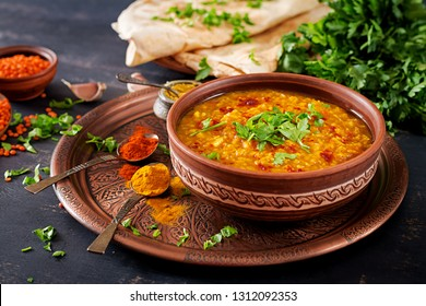 Indian dal. Traditional Indian soup lentils.  Indian Dhal spicy curry in bowl, spices, herbs, rustic black wooden background. Authentic Indian dish. Overhead