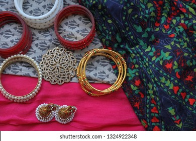 Indian decorations for dancing: bracelets, earrings for dancing bharatanatyam or kathak. Fabric background. Top view. Place for text.