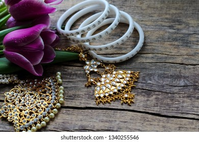 Indian decorations for dancing kathak: bracelets, necklace. Purple ultraviolet tulips on old rustic wooden background. Mothers, Womens Day and greeting concept. Top view. Copy space. Place for text