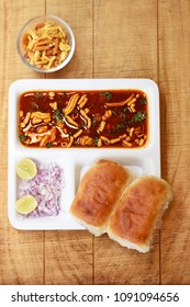 """Indian delicious """"Misal Pav"""" with onion and coriander spread on top of curry wheat bread"""
