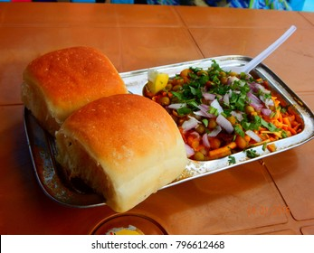 "Indian delicious ""Misal Pav"" with onion and coriander spread on top of curry wheat bread"