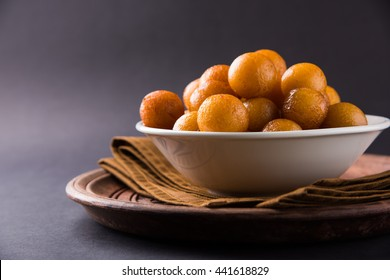 indian dessert gulab jamun served in a white ceramic bowl and wooden tray with table napkin