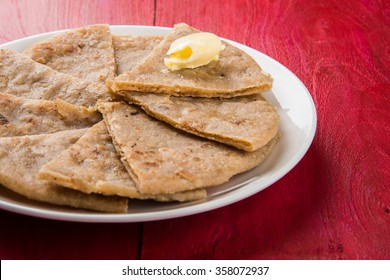 Indian dessert sweet Hot Mawa / Khoya Roti with ghee also known as Khavyachi Poli in Marathi, served in a plate over colourful or wooden background. Selective focus