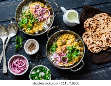 Indian dhal with jasmine rice, marinated red onion, coriander and whole grain flatbread on dark background, top view. Flat lay