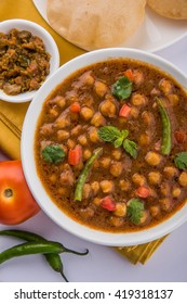Indian dish spicy Chick Peas curry also known as Chola/Chana Masala or commonly Chole, served served with fried puri over colourful or wooden background. Selective focus