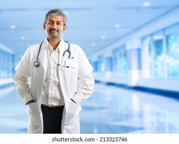 Indian doctor. Mature Indian male medical doctor standing inside hospital. Handsome Indian model portrait.