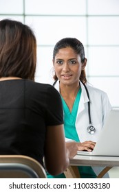 Indian doctor talking with female patient in doctors office.