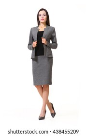indian eastern brown hair business executive woman with straight hair style in office gray skirt suit jacket high heel sandals shoes going full body length isolated on white