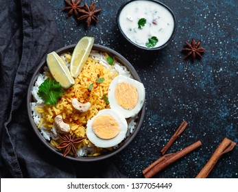 Indian Egg Biryani or anda rice top view on dark background. Egg Biryani - Basmati rice cooked with masala roasted eggs and spices, served with yogurt. Copy space for text