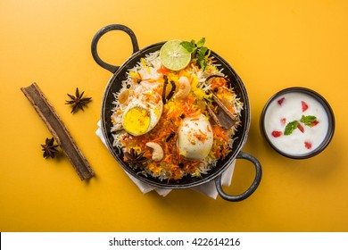 Indian Egg Biryani or anda rice served in kadhai or kadai with yogurt dip, selective focus