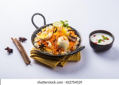 Indian Egg Biryani or anda rice served in kadhai or kadai with yogurt dip, selective focus