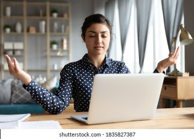Indian employee sit at workplace desk relaxing do yoga asana practice with eyes closed folded fingers makes mudra gesture. No psychological stress at workday, fatigue relief, healthy lifestyle concept