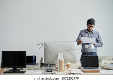 Indian It engineer analyzing document with statistics