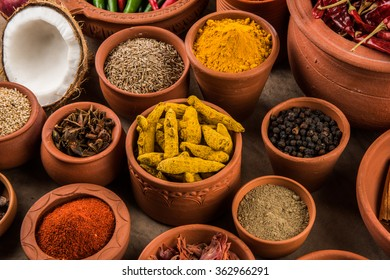 Indian essential spices in terracotta pots arranged over textured background, selective focus