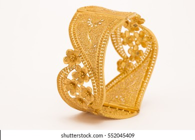 Indian ethnic designed gold bangles in white background.