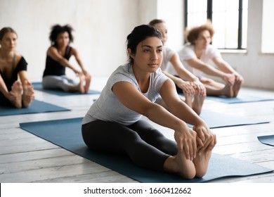 Indian ethnicity instructor and diverse group of people sitting on mats performing Seated Forward Bend at morning work out activity, physical and mental health care, wellness healthy lifestyle concept