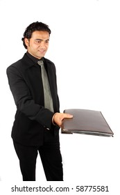 An Indian executive handing over a project file, on white studio background.