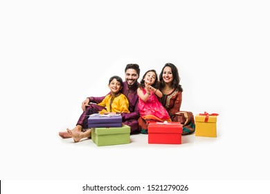 Indian family celebrating Diwali / Deepavali in traditional wear while sitting isolated over white background with gift boxes and lamp in thali