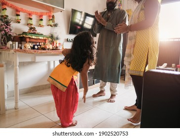 Indian family celebrating a traditional hindu event at home and dancing together in living room - Parents and child