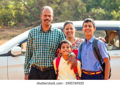 indian family driving boys to school In front of house gates